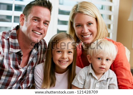 Portrait Of Family Sitting On Sofa At Home - stock photo