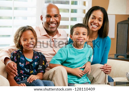 Portrait Of Family Sitting On Sofa Together - stock photo