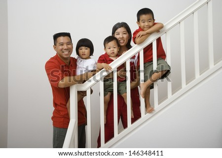 Portrait of family standing on stairs - stock photo