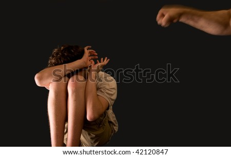 portrait of family violence - father's fist aims at young teenage son - stock photo