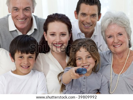 Portrait of family watching television at home - stock photo