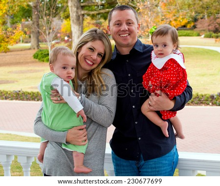 Portrait of family with twin babies at home on front porch