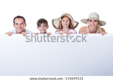 Portrait Of Family With Two Children Behind Blank Board On White Background - stock photo