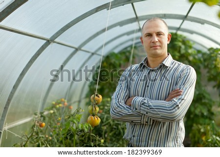 Portrait of  farmer  in greenhouse - stock photo