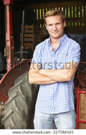 Portrait Of Farmer With Old Fashioned Tractor - stock photo