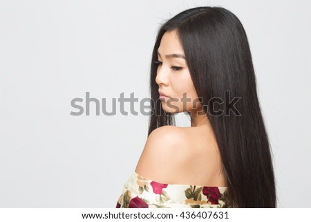 Portrait of fashion asian lady in spring or summer dress looking away. Brunette lady showing her gorgeous hair to camera in studio. - stock photo