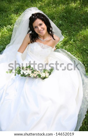 Portrait of fashion bride with bunch of flowers sitting on the grass