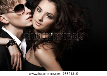 portrait of fashion couple on black background - stock photo