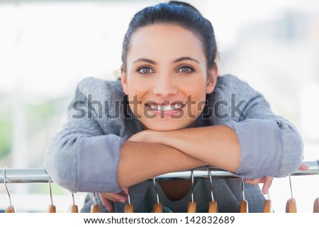 Portrait of fashion designer leaning on clothes and looking at camera - stock photo