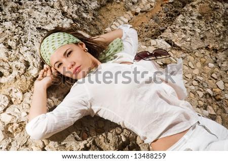 Portrait of fashion female lying on rock background - stock photo