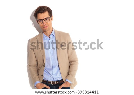 portrait of fashion guy wearing glasses, posing with both hands in pockets while smiling at the camera in isolated studio background - stock photo