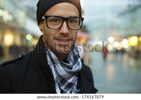 Portrait of fashion man on street, blurred city background - stock photo