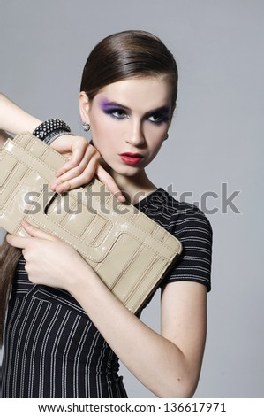 Portrait of fashion model holding purse posing on gray background