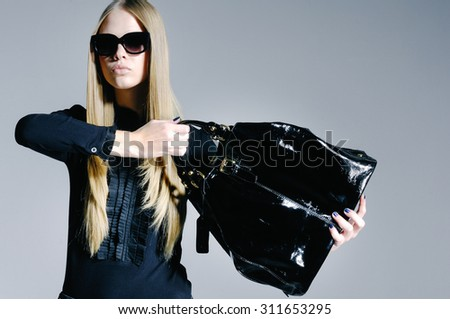 portrait of fashion model in modern clothes holding handbag â??gray background - stock photo