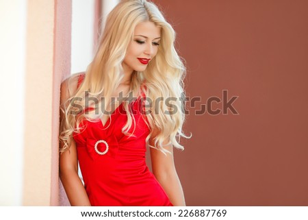 Portrait Of Fashion Woman In red Dress Outdoor. Fashion woman walking in the street