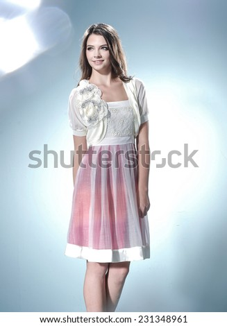 Portrait of fashion young woman standing-light background - stock photo