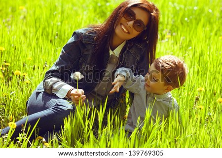 Portrait of fashionable baby boy and his gorgeous mother in trendy sunglasses playing with dandelion in the park. Sunny spring day. Outdoor shot - stock photo