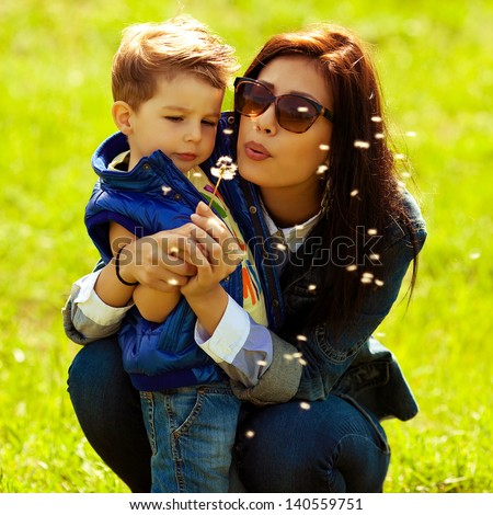 Portrait of fashionable baby boy and his gorgeous mother in trendy sunglasses playing with dandelion in the park. Sunny spring day. Hipster style. Outdoor shot - stock photo