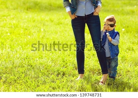 Portrait of fashionable baby boy in trendy sunglasses and his mother standing in the park. Sunny spring day. Hipster style. Copy-space. Outdoor shot - stock photo