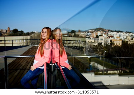 Portrait of fashionable caucasian woman with long beautiful hair dressed in hipster clothing looking at you,attractive young teenager girl dressed in pink sweater posing outdoors in a sunny summer day - stock photo
