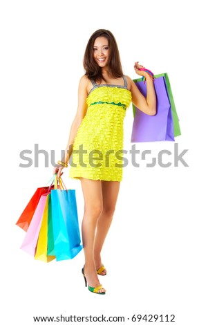 Portrait of fashionable female in yellow glamorous dress with colorful paperbags - stock photo
