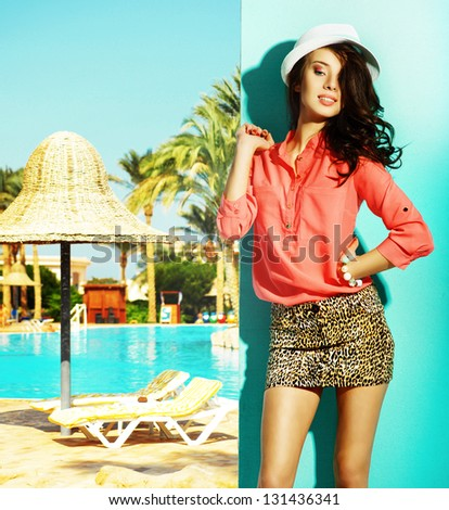 Portrait of fashionable girl with summer hat on her head next to swimming pool - stock photo