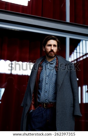 Portrait of fashionable hipster man dressed in elegant coat standing indoors look into the distance - stock photo