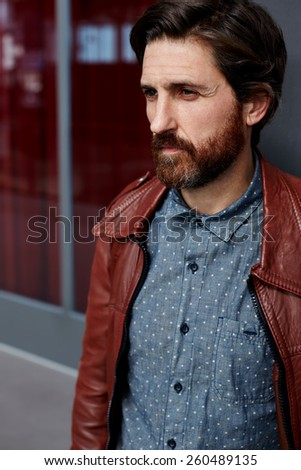 Portrait of fashionable hipster man dressed in pattern shirt and leather jacket standing indoors with beautiful glassy wall on background - stock photo