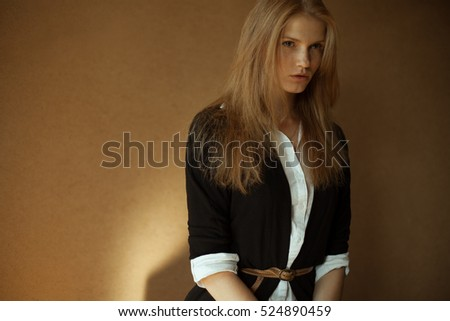 Portrait of fashionable model with long red hair in black jacket, white shirt, posing over wooden background. Natural style. Daylight. Copy-space. Studio shot