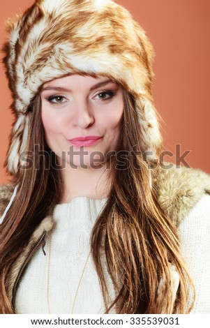 Portrait of fashionable pretty woman in fur winter cap hat on orange background in studio.
