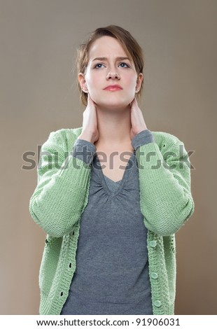 Portrait of fashionable young brunette woman showing symptoms of neck pain. - stock photo