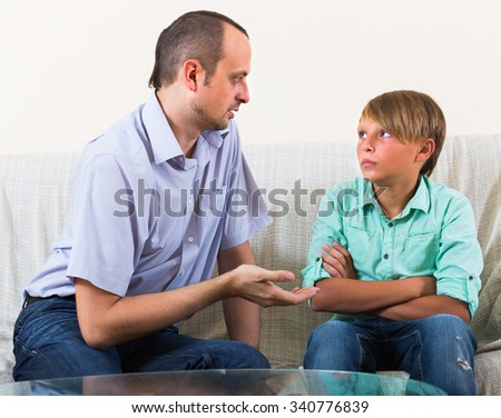 Portrait of father and boy having important conversation - stock photo