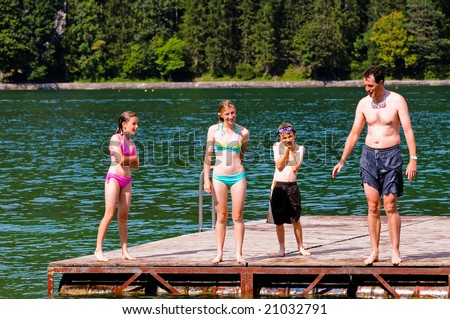 portrait of father and children swimming in the lake - stock photo