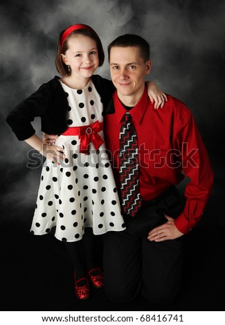 Portrait of father and daughter dressed up in red, black, and white hugging - stock photo