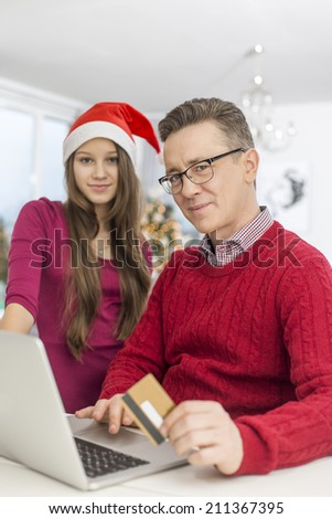 Portrait of father and daughter shopping online during Christmas - stock photo