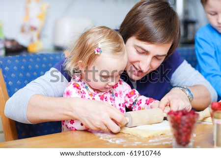 Portrait of father and his little daughter in kitchen baking together - stock photo