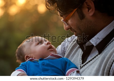 portrait of father and son against nature background, Indian man holding his son in lap. - stock photo