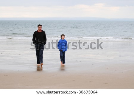 portrait of father and son on beach - stock photo