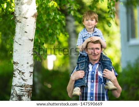 Portrait of father and son outdoors. - stock photo