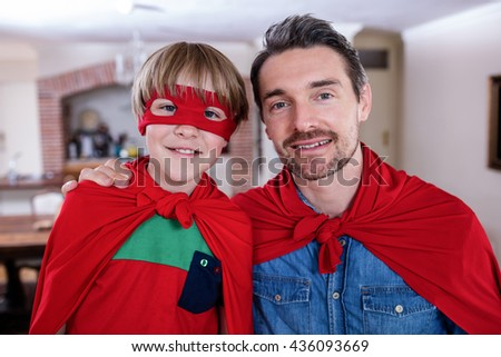 Portrait of father and son pretending to be superhero in living room at home - stock photo
