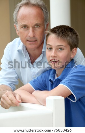 Portrait of father and son sitting in sofa - stock photo