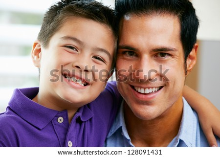 Portrait Of Father And Son Sitting On Sofa At Home - stock photo