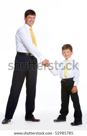 Portrait of father and son standing and handshaking while looking at camera on white background - stock photo