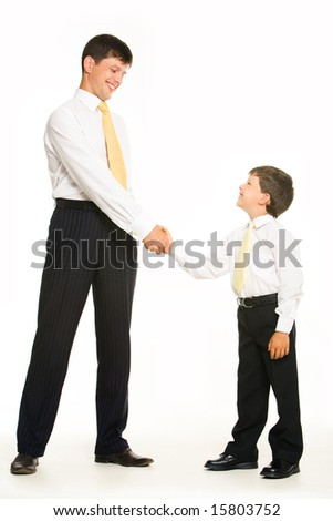 Portrait of father and son standing and handshaking while looking at each other on white background - stock photo