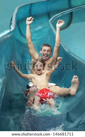 Portrait of father and son with arms outstretched on water slide - stock photo