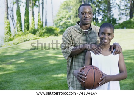 Portrait of father and son with basketball - stock photo