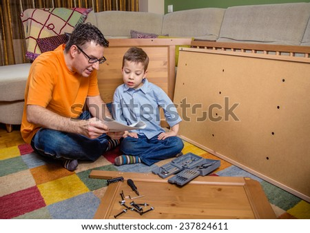 Portrait of father and son with tools reading the instructions to assemble a new furniture for home. Family leisure concept - stock photo