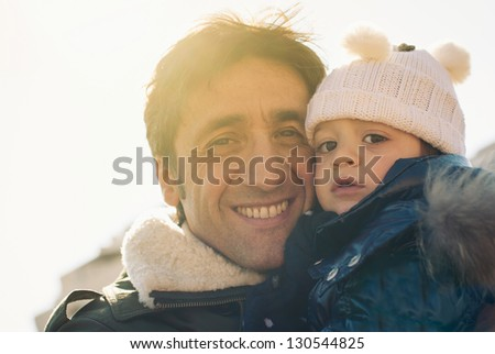 Portrait of father and young daughter outdoors In the park. Back light sun. - stock photo