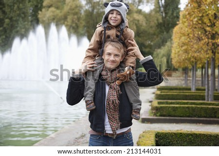 Portrait of father carrying son on his shoulders at park - stock photo