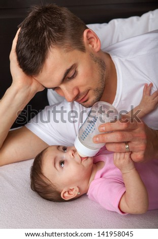 Portrait of father feeding daughter at home - stock photo